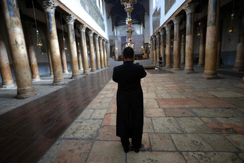 A priest stands inside the deserted Church of the Nativity in the occupied West Bank town of Bethlehem