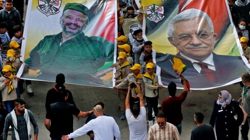 Palestinian Fateh movement supporters carry portraits of their current leader Mahmud Abbas (R) and his late predecessor Yasser Arafat (L) during a march to mark the 16th anniversary of Arafat's death in the village of Dura, near the West Bank city of Hebron