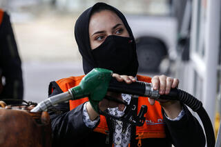 Salma al-Najjar, a 16-year-old Palestinian who works at a petrol station to help her family with income, adds fuel into a jerrycan in Khan Yunis in southern Gaza Strip