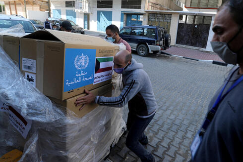 A worker unloads boxes containing ventilators delivered by the World Health Organization (WHO) and donated by Kuwait, in Gaza City