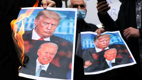 Protesters burn pictures of U.S. President-elect Joe Biden and U.S. President Donald Trump during a demonstration against the killing of Mohsen Fakhrizadeh,