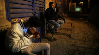 Palestinian youth smokes as another uses his mobile phone in an alley at night in Jerusalem's Old City amid coronavirus crisis