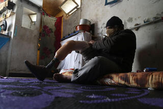 Syrian refugee Ahmad, 54, adjusts his artificial limb at his house in the town of Daraya, southeast of Beirut, Lebanon
