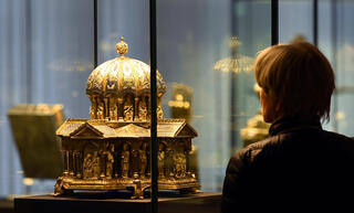 """A visitor looks at the the cupola reliquary (Kuppelreliquar) of the so-called """"Welfenschatz"""" (Guelph Treasure) displayed at the Kunstgewerbemuseum (Museum of Decorative Arts) in Berlin"""