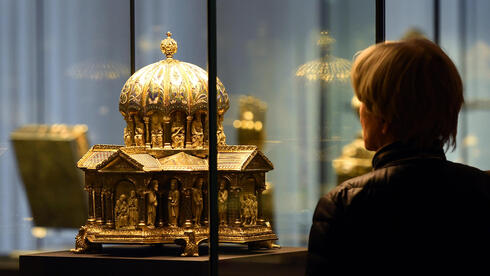"A visitor looks at the the cupola reliquary (Kuppelreliquar) of the so-called ""Welfenschatz"" (Guelph Treasure) displayed at the Kunstgewerbemuseum (Museum of Decorative Arts) in Berlin"