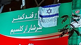 Israeli flag, banner saying 'thank you Mossad' hanging on a billboard in Tehran after the assassination of Iranian nuclear scientist Mohsen Fakhrizadeh
