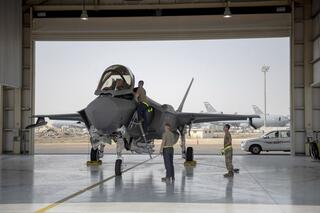 An F-35 fighter jet pilot and crew prepare for a mission at Al-Dhafra Air Base in the United Arab Emirates