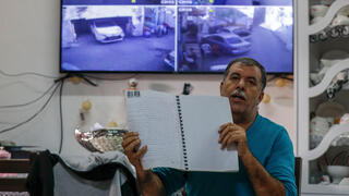 Zuheir Rajabi, sitting in front of a flat-screen displaying live footage from 10 surveillance cameras set up around his home, shows a document from the Jordanian authorities proving his ownership of the house