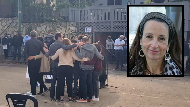 The family of murdered Esther Horgan huddles as her funeral begins at the Tal Menashe settlement