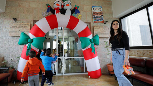 A staff member looks on as children play at The Creche, a house sheltering children, in Bethlehem