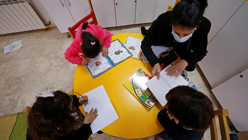 A staff member teaches children at The Creche, a house sheltering children, in Bethlehem
