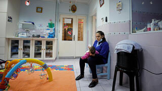staff member feeds an infant at The Creche, a house sheltering children, in Bethlehem
