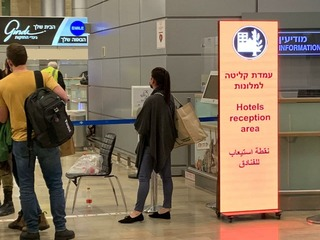 Israelis who returned from Dubai wait at Ben-Gurion Airport for transportation to a government-run isolation center