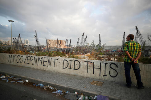 A man stands next to graffiti at the damaged port area in the aftermath of a massive explosion in Beirut, Lebanon