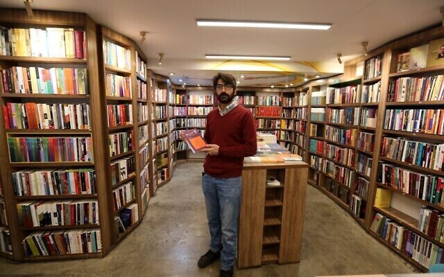 Manager Reza Bahrami poses for a picture at a bookstore of the Nashre-Cheshmeh Publishing House on Karim Khan street in the Iranian capital Tehran