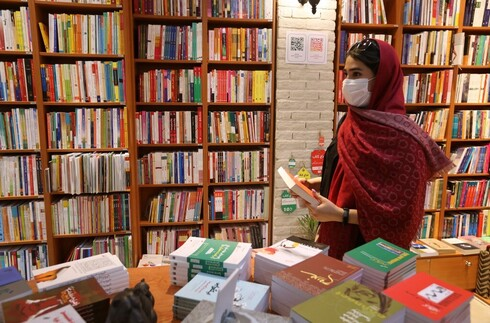 A woman picks a book at a bookstore on Enqelab (Revolution) street in Iran's capital Tehran
