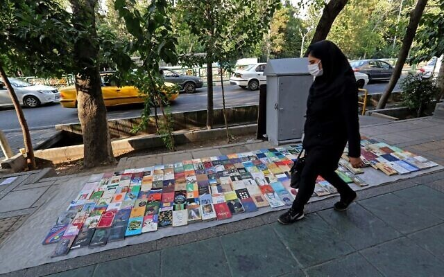 A woman walks past books displayed for sale along a pavement on Enqelab (Revolution) street in Iran's capital Tehran