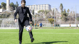 Moshe Hogeg, one of the owners of Beitar Jerusalem FC soccer club, plays with a ball, in the team training ground in Jerusalem