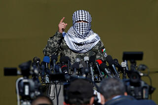A Palestinian militant gestures as he speaks to the media during the first-ever joint exercise by Gaza's terror groups, Dec. 2020