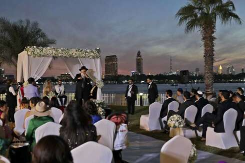 A rabbi officiates under a traditional Jewish wedding canopy during marriage ceremony of the Israeli couple Noemie Azerad, left sited under the canopy, and Simon David Benhamou, at a hotel in Dubai, United Arab Emirates