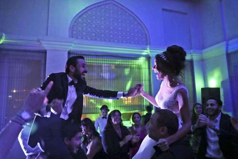 Israeli couple Noemie Azerad, right, and her husband Simon David Benhamou grasp each others hands on the shoulders of skullcap-wearing groomsmen during their wedding party at a hotel in Dubai, United Arab Emirates