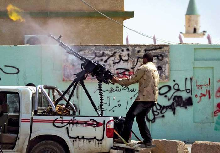 "A rebel firing a gun in the heavily contested city of Ajdābiyā in eastern Libya, March 6, 2011. The graffiti on the side of the truck reads, ""Army of Libya"""