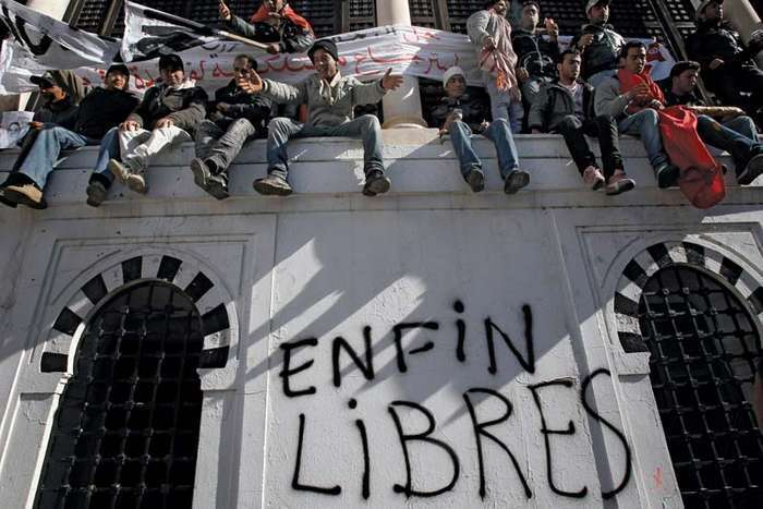 "Demonstrators in the capital city of Tunis sitting on a wall where ""Free at last"" was written after the popular unrest of the Jasmine Revolution forced Tunisian Pres. Zine al-Abidine Ben Ali to step down, January 2011"