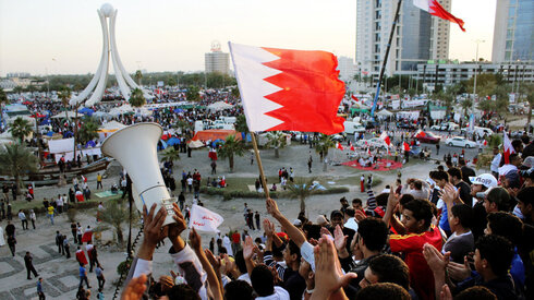 Protesters wave flags at the Pearl Roundabout in the capital Manama on Feb. 20, 2011