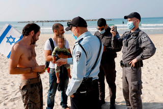 Police officers on Tel Aviv beach enforcing the country's third lockdown