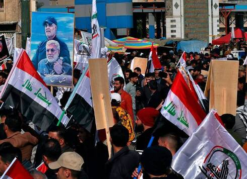 Supporters of the Popular Mobilization Forces hold a poster of Abu Mahdi al-Muhandis, deputy commander of the Popular Mobilization Forces, front, and General Qassem Soleimani, head of Iran's Quds force during a protest, in Tahrir Square, Iraq