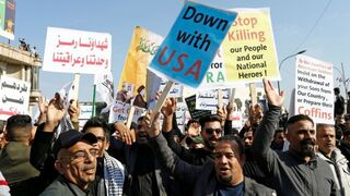 Iraqis, including supporters of Hashid Shaabi (Popular Mobilization Forces), hold placards as they gather to mark the one year anniversary of the killing of senior Iranian military commander General Qassem Soleimani and Iraqi militia commander Abu Mahdi al-Muhandis in a U.S. attack, in Baghdad, Iraq