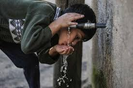 A boy drinking water out of a tap in Gaza