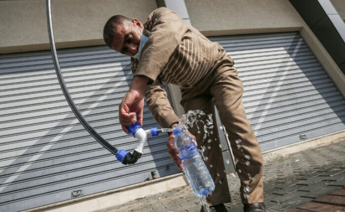 A Palestinian man filling a bottle with water produced by the Watergen technology in Gaza