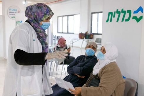 A healthcare worker speaks to an Arab Israeli woman before giving her a Covid-19 vaccine