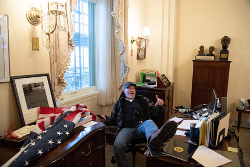 A supporter of President Donald Trump sits inside the office of U.S. Speaker of the House Nancy Pelosi as he protests inside the U.S. Capitol