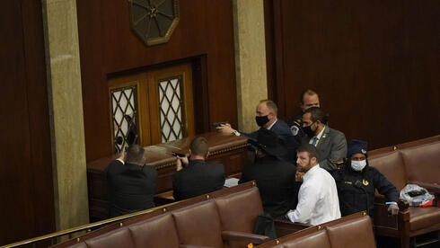 U.S. Capitol police officers point their guns at a door that was vandalized in the House Chamber during a joint session of Congress