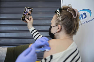 An Israeli woman takes a selfie as she receives her COVID vaccine in Tel Aviv