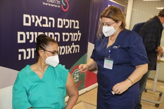A member of the medical staff receiving the coronavirus vaccine at Sheba Medical Center near Tel Aviv