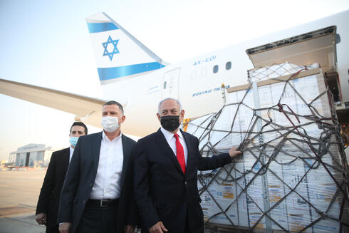 Health Minister Yuli Edelstein and Prime Minister Benjamin Netanyahu next to a shipment of Pfizer's coronavirus vaccine at Ben Gurion Airport