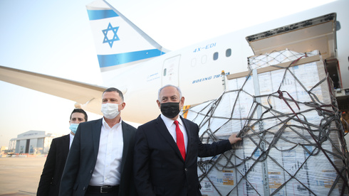 Benjamin Netanyahu and Health Minister Yuli Edelstein greet a plane carrying Pfizer vaccines as it arrives at Ben-Gurion Airport