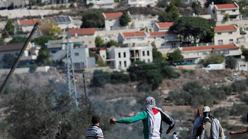 Palestinian demonstrators stand in front of a Jewish settlement during a protest, in Kafr Qaddum in the West Bank