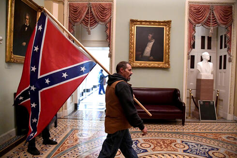 A Trump supporter carries a Confederate flag in the U.S. Capitol after a mob stormed the building, Jan. 6, 2021
