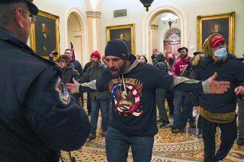 Iowan Trump supporter Doug Jensen, clad in a QAnon sweatshirt, gestures to a Capitol Police officer after storming the building on Jan. 6, 2021