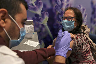 A woman is inoculated against coronavirus at a vaccination center in Jerusalem