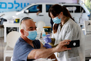 A man taking a selfie while being inoculated for coronavirus at a Maccabi HMO vaccination center in Haifa