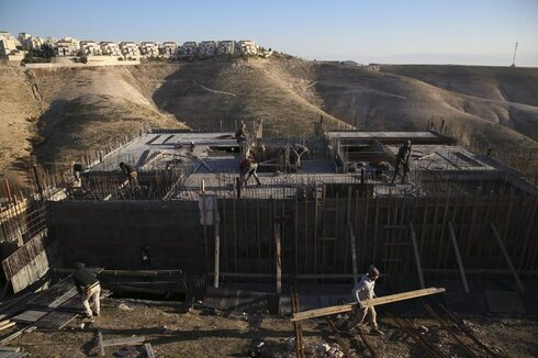Palestinian laborers work at a construction site in the Israeli settlement of Maale Adumim, near Jerusalem