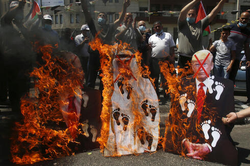 Palestinians burn pictures of U.S. President Donald Trump, Abu Dhabi Crown Prince Mohammed bin Zayed al-Nahyan and and Prime Minister Benjamin Netanyahu during an August 2020 West Bank protest against the United Arab Emirates' deal with Israel