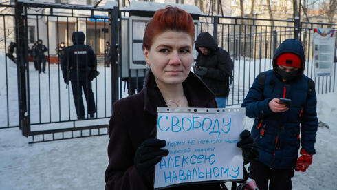 A woman holds a poster 'Freedom for Alexei Navalny' outside the police station where detained Russian opposition leader and anti-corruption activist Alexei Navalny is held