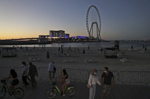 Tourists and residents enjoy the sunset at the Jumeirah Beach Residence, in Dubai, United Arab Emirates
