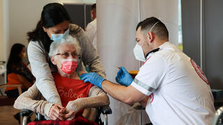 The resident of a nursing home in Netanya holds the hand of her care giver as she receives the coronavirus vaccine